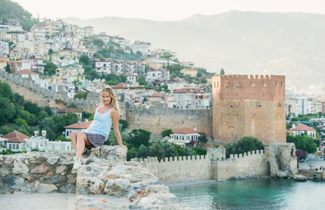 Blond woman sitting on ancient fortress wall  Alanya castle  Turkey