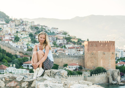 Young blond woman tourist relaxing on ancient fortress wall of Alanya castle Kizil Kule or Red Tower at background