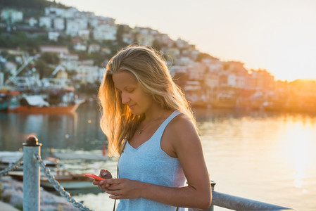 Young blond woman texting message at sunset  Alanya  Turkey