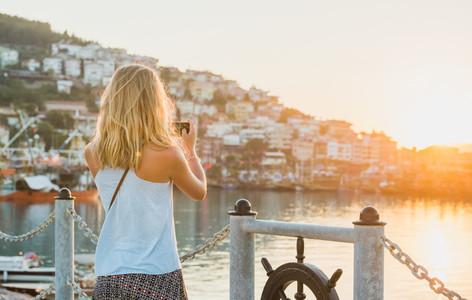 Young blond tourist woman making photo of sunset Alanya Turkey