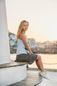 Young blond woman enjoying sunset and sitting on bench of the Alanya039s Lighthouse near the water