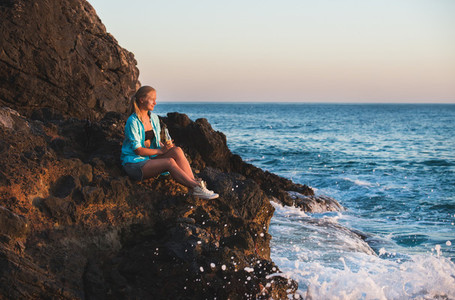 Young blond woman tourist sittig on rocks by the sea at sunset with bottle of lemonade  Alanya  Mediterranean region  Turkey