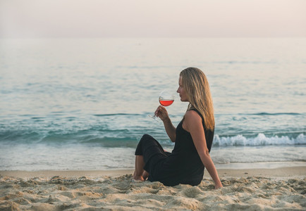Young blond woman enjoying glass of rose wine on beach near the sea at sunset
