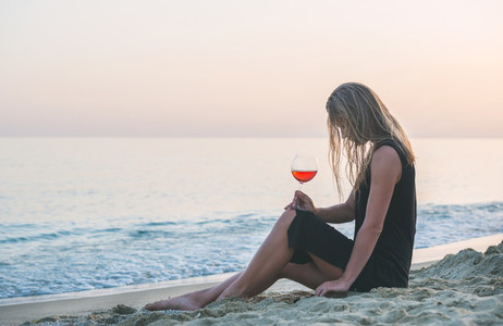 Young blond woman relaxing with glass of rose wine on beach by the sea at sunset