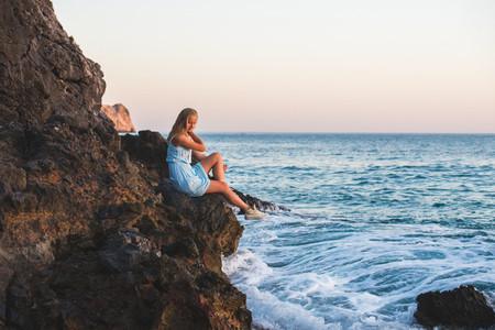 Young blond woman tourist in blue dress sittig on rocks by the sea at sunset  Alanya  Mediterranean region  Turkey