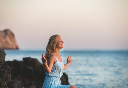 Young blond woman tourist in blue dress relaxing  meditating and smiling on stone rocks by the wavy sea at sunset  Alanya  Mediterranean region  Turkey