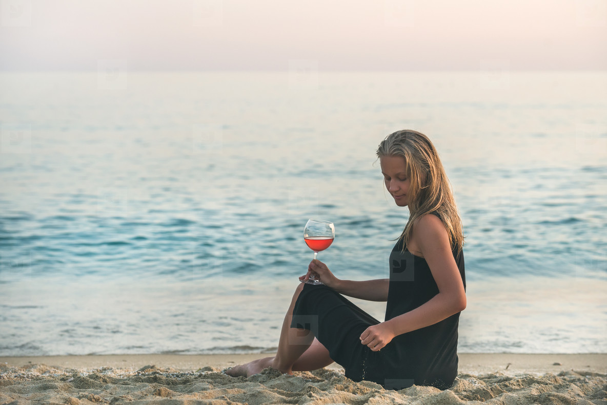 Young blond woman sitting with glass of rose wine on beach by the sea at sunset