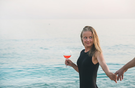 Young blond woman holding glass of rose wine and man039 s hand on beach by the sea at sunset  Alanya  Turkey