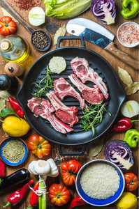Ingredients for cooking healthy meat dinner  Raw uncooked lamb chops in iron grill pan with vegetables  rice  herbs and spices over rustic wooden background  Top view