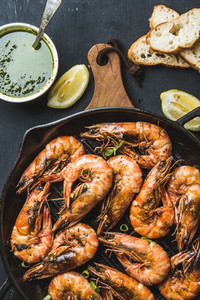 Roasted tiger prawns in iron pan on wooden board with fresh leek lemon slices bread and pesto sauce over black background