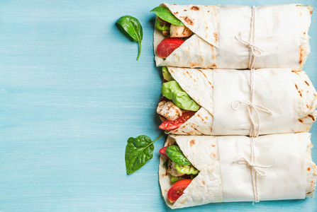 Healthy lunch snack  Three tortilla wraps with grilled chicken fillet and fresh vegetables over turquoise blue painted wooden background  Top view  copy space