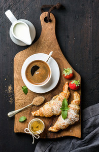 Breakfast set  Two freshly baked croissants with strawberries  honey  cup of black coffee  pitcher and spoon on rustic wooden board over dark background