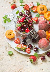 Healthy summer fruit variety  Sweet cherries in glass jar  strawberries  peaches  apricots and mint leaves on white ceramic serving plate over light concrete background  Top view  selective focus