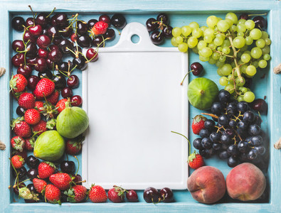Healthy summer fruit variety  Figs  black and green grapes  sweet cherries  strawberries  peaches on blue painted wooden background with white ceramic board in center  copy space