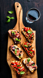Brushetta set and glass of red wine Small sandwiches with prosciutto tomatoes parmesan cheese fresh basil balsamic creme on rustic wooden board