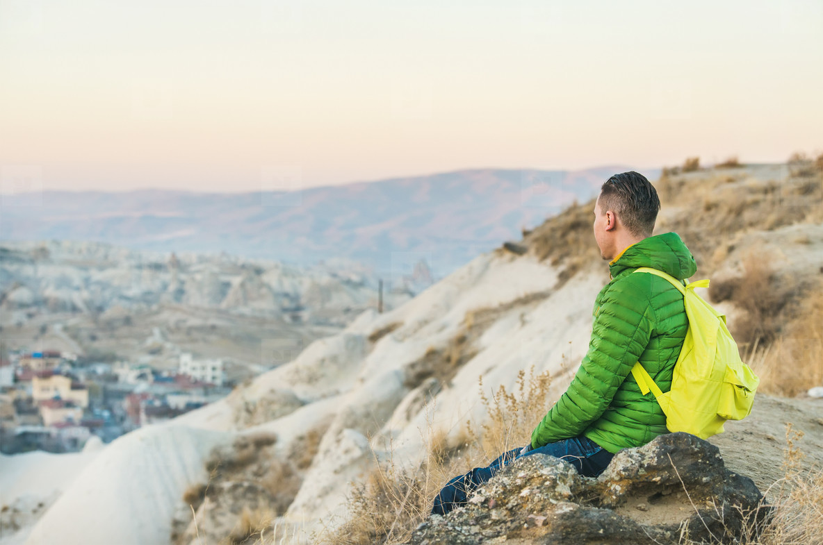 Young man sitting at edge of cliff  Cappadocia  Central Turkey