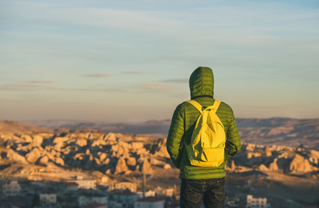 Young man in bright clothing watching sunrise  Cappadocia  Central Turkey
