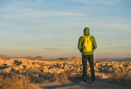 Young man in bright clothing standing in mountains  Cappadocia  Turkey