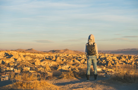Young woman traveller in hoodie watching sunrise  Cappadocia  Central Turkey