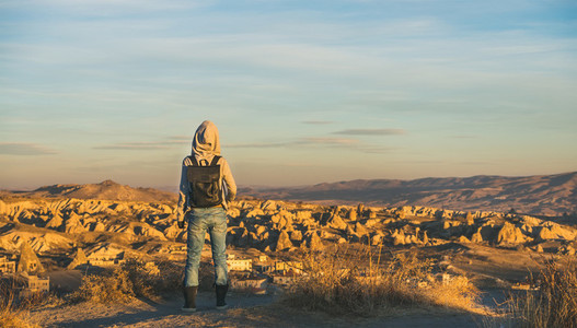 Young woman traveler with backpack watching sunrise Cappadocia Central Turkey