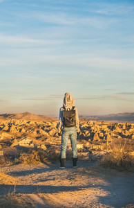 Young woman traveller standing and watching sunrise  Cappadocia  Central Turkey
