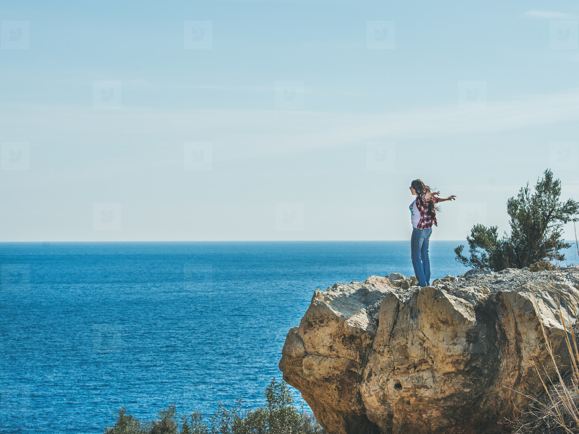Young happy girl traveler standing on rock over sea  Turkey