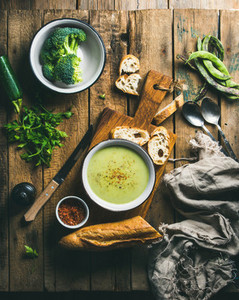 Fresh homemade pea broccoli zucchini cream soup with baguette