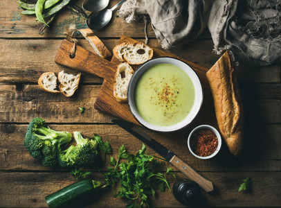 Homemade pea  broccoli  zucchini cream soup with fresh baguette