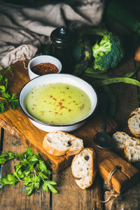 Homemade pea  broccoli  zucchini cream soup with baguette slices