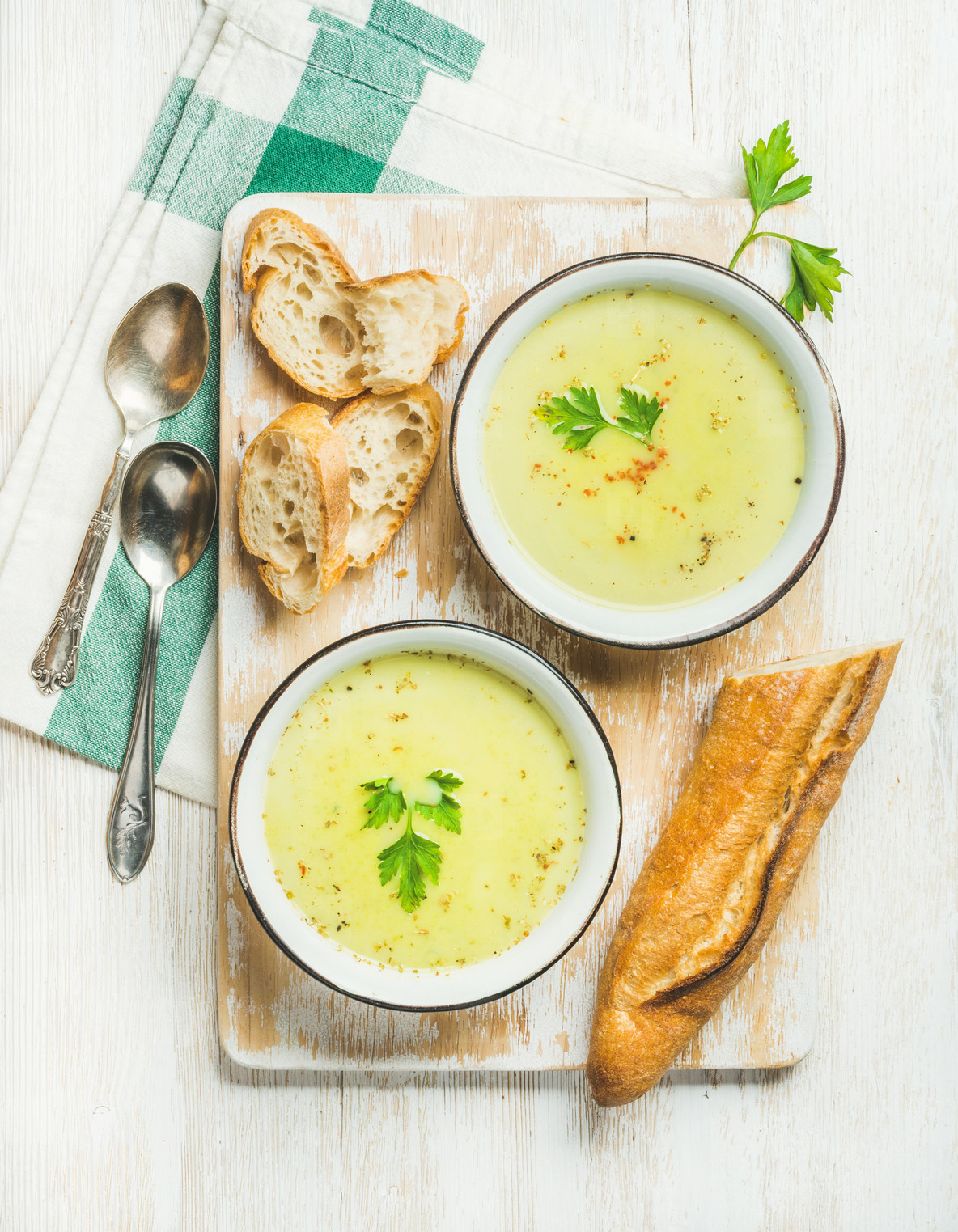 Green vegetable soup with parsley and baguette on wooden board
