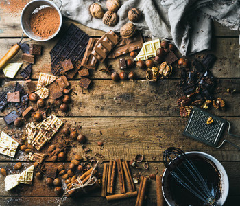 Background with chocolate nuts and spices over wooden backdrop