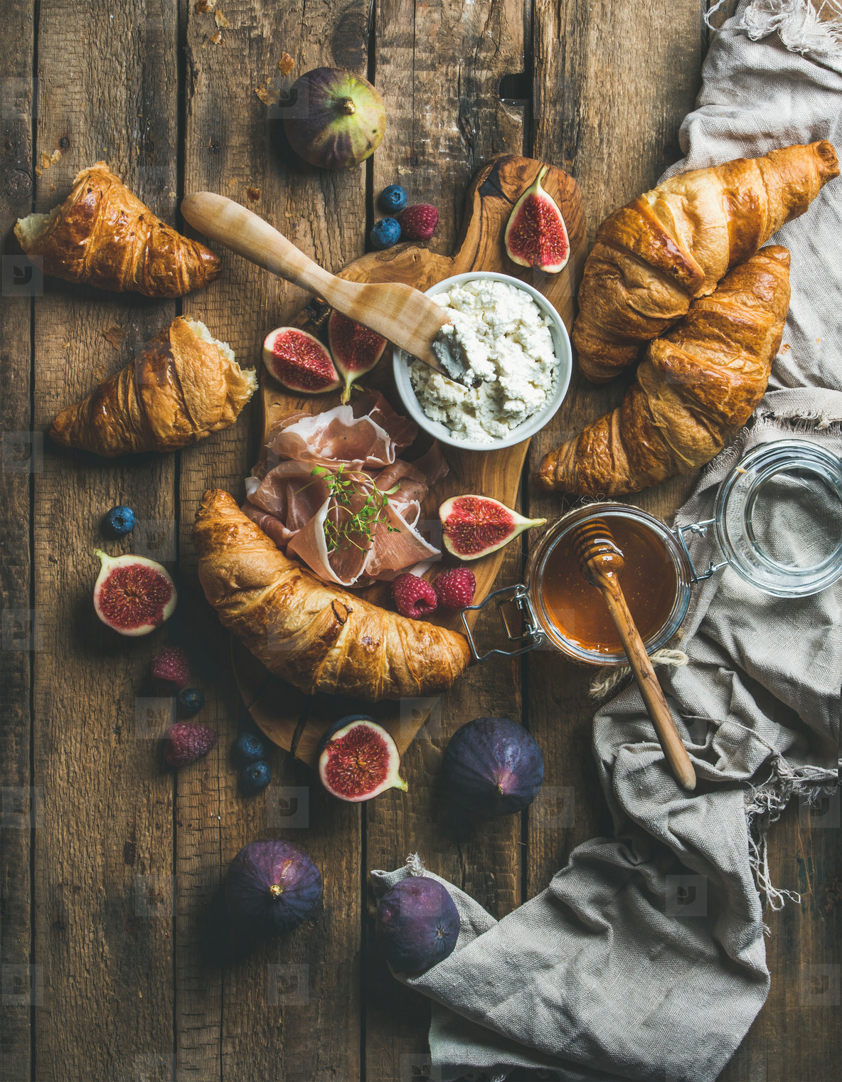 Breakfast with croissants  honey  ricotta cheese  fresh berries and prosciutto