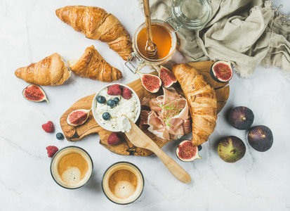Breakfast with croissants ricotta coffee and berries over white background