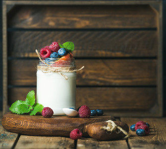 White yogurt in jar with fresh berries  peach  mint leaves