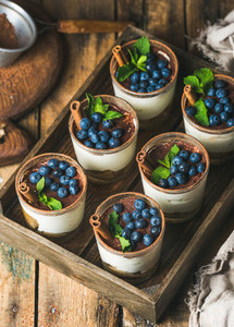 Tiramisu dessert with cinnamon mint and blueberry in wooden tray