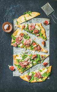 Fig prosciutto arugula and sage flatbread pizza cut into pieces