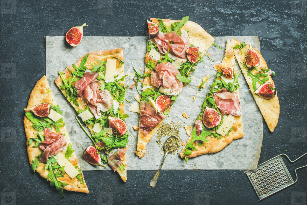 Fig  prosciutto  arugula and sage flatbread pizza on dark background