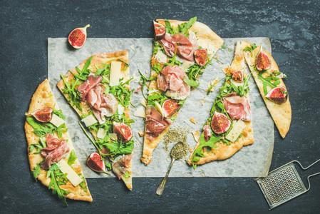 Fig  prosciutto  arugula and sage flatbread pizza on dark background