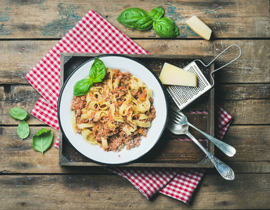 Tagliatelle Bolognese with Parmesan and basil in wooden tray