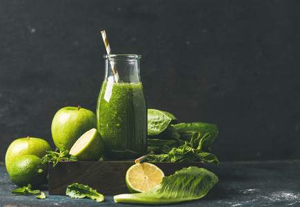 Smoothie with apple  romaine lettuce  lime  mint  dark blue background