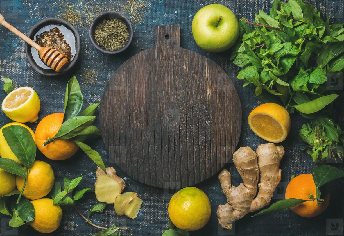 Oranges  mint  lemons  ginger  honey  apple  wooden board in center
