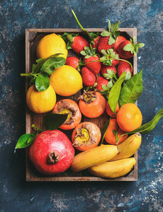 Oranges  lemons  pomegranate  bananas  strawberries and persimmon in wooden box