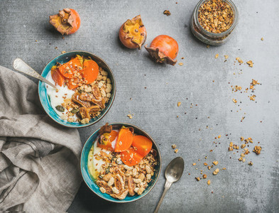 Healthy vegetarian breakfast in colorful bowls over grey concrete background