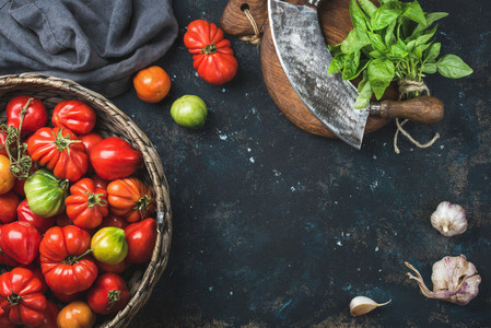 Fresh colorful ripe heirloom tomatoes in basket copy space