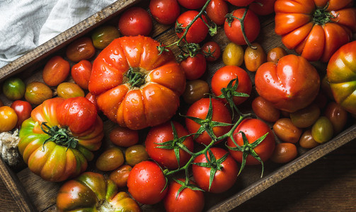 Colorful tomatoes of different sizes and kinds in dark wooden tray