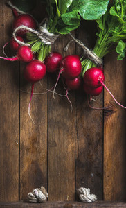 Fresh radish banches on wooden tray background  copy space