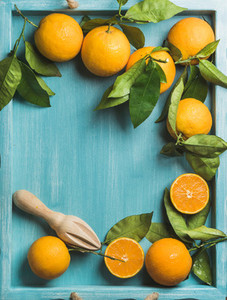 Fresh oranges with leaves on blue painted wooden background  copy space
