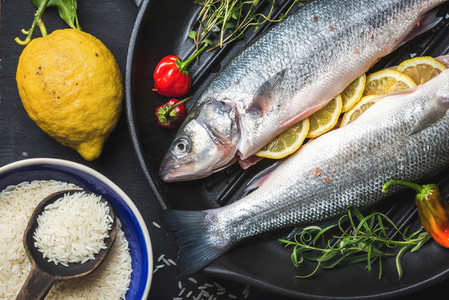 Raw uncooked seabass with rice  lemon  herbs and spices on black grilling iron pan over dark background