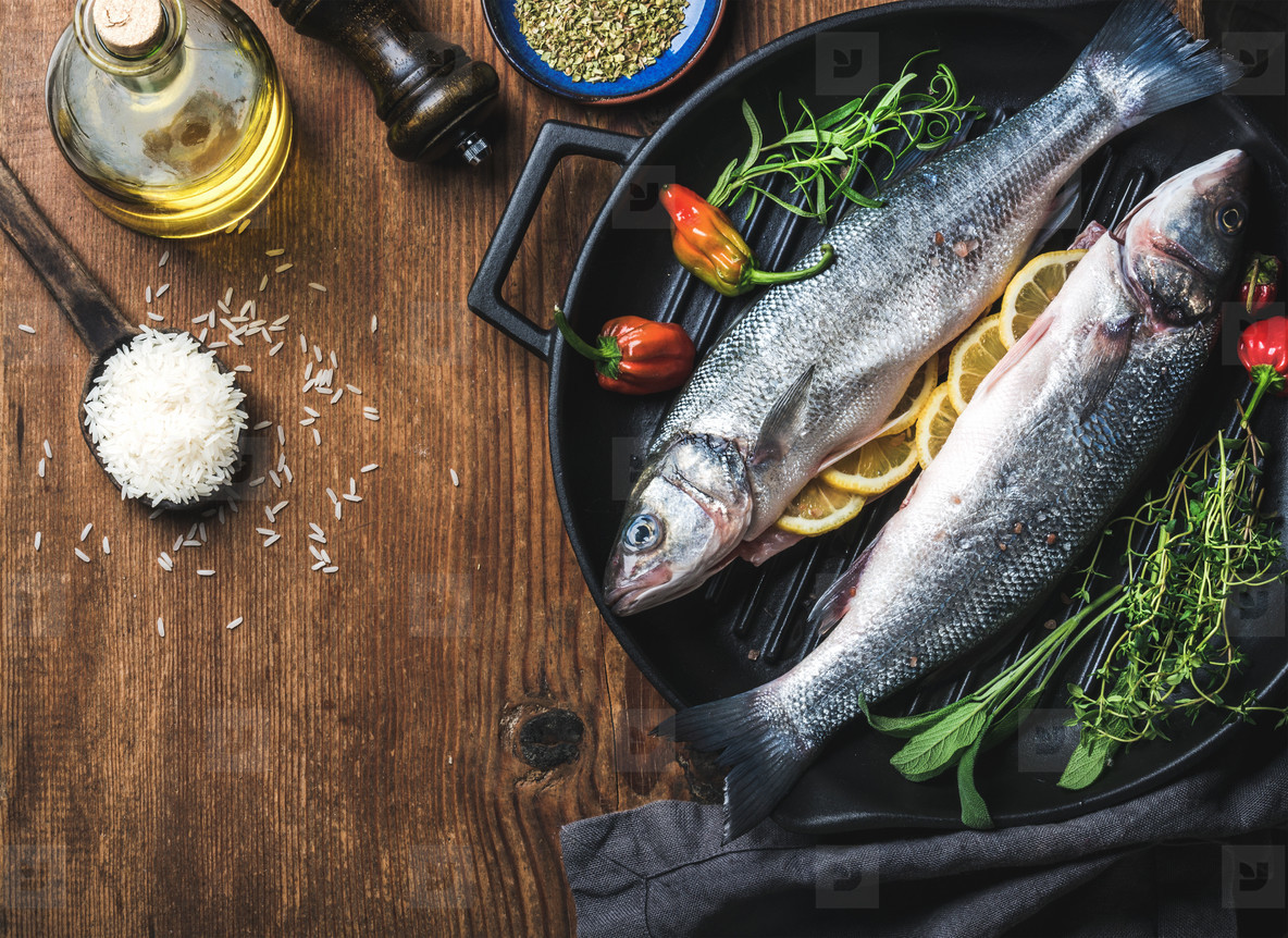 Ingredients for cookig healthy fish dinner  Raw uncooked seabass  with rice  olive oil  lemon slices  herbs and spices on black grilling iron pan over rustic wooden background