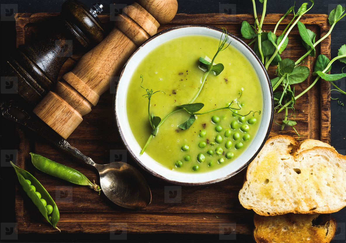 Fresh homemade pea cream soup in bowl with grilled bread